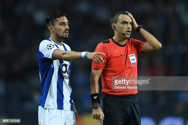 Alex Telles of FC Porto and the referee Ovidiu Hategan in action during the UEFA Champions League group G match between FC Porto and RB Leipzig at...