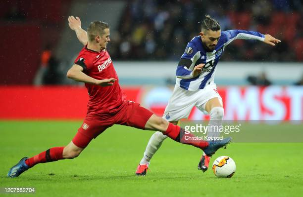 Alex Telles of Porto is challenged by Lars Bender of Bayer 04 Leverkusen during the UEFA Europa League round of 32 first leg match between Bayer 04...