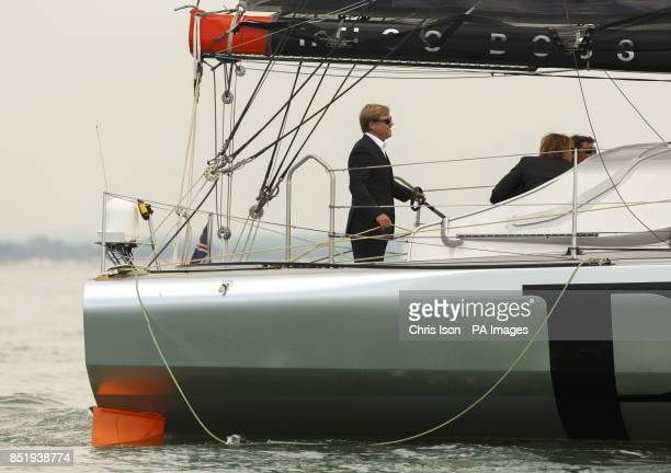 Alex Thomson sails his Open 60 racing yacht Hugo Boss dressed in a suit during the Artemis Challenge at Aberdeen Asset Management Cowes Week