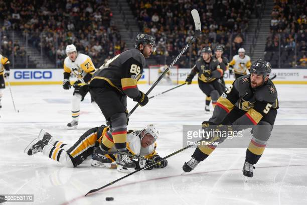 Alex Tuch and Deryk Engelland of the Vegas Golden Knights battle for the puck with Patric Hornqvist of the Pittsburgh Penguins during the game at...