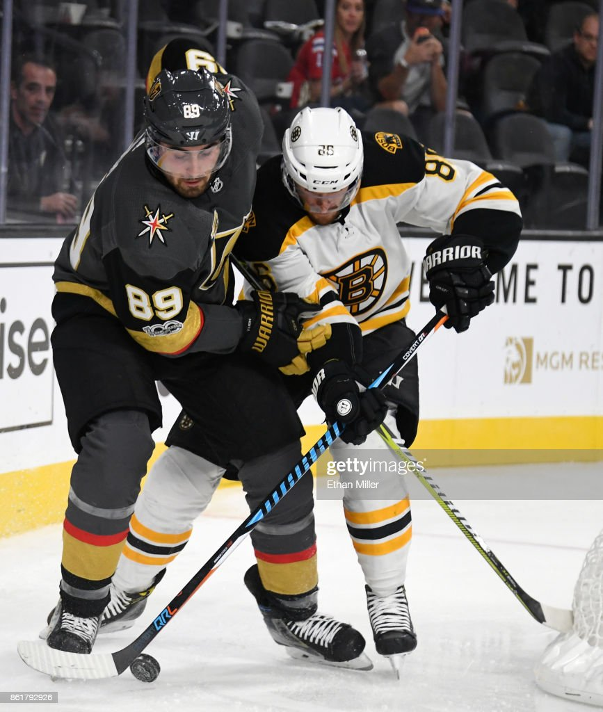 Alex Tuch #89 of the Vegas Golden Knights and Kevan Miller #86 of the Boston Bruins battle for the puck behind the net in the second period of their game at T-Mobile Arena on October 15, 2017 in Las Vegas, Nevada. The Golden Knights won 3-1.