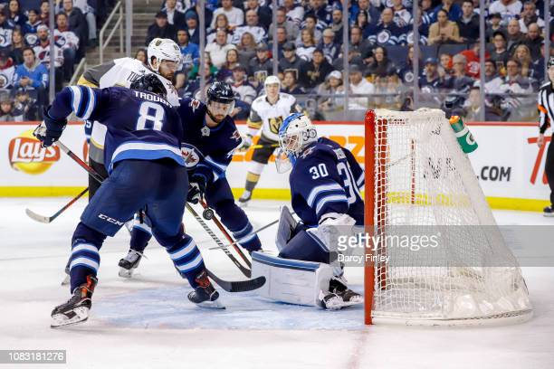 Alex Tuch of the Vegas Golden Knights Jacob Trouba Josh Morrissey and goaltender Laurent Brossoit of the Winnipeg Jets keep an eye on the loose puck...