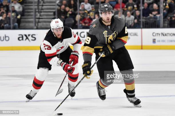 Alex Tuch of the Vegas Golden Knights skates with the puck while Stefan Noesen of the New Jersey Devils defends during the game at TMobile Arena on...