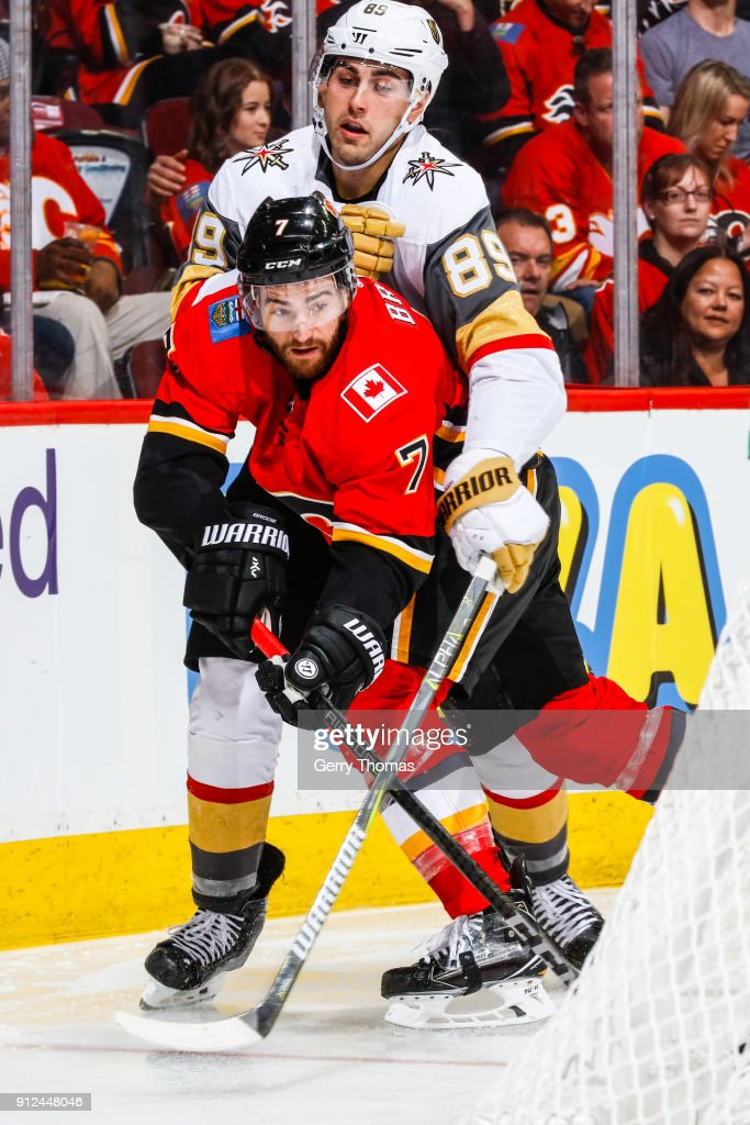 Alex Tuch #89 of the Vegas Golden Knights tries to get the puck from TJ Brodie #7 of the Calgary Flames in an NHL game on January 30, 2018 at the Scotiabank Saddledome in Calgary, Alberta, Canada.