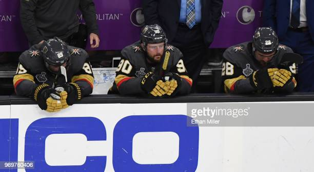 Alex Tuch Tomas Tatar and William Carrier of the Vegas Golden Knights sit on the bench as they watch the Washington Capitals celebrate their 43 win...