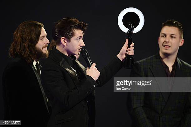 Alex Turner Nick O'Malley and Matt Helders of Arctic Monkeys receive the award for the MasterCard British Album of the Year at The BRIT Awards 2014...