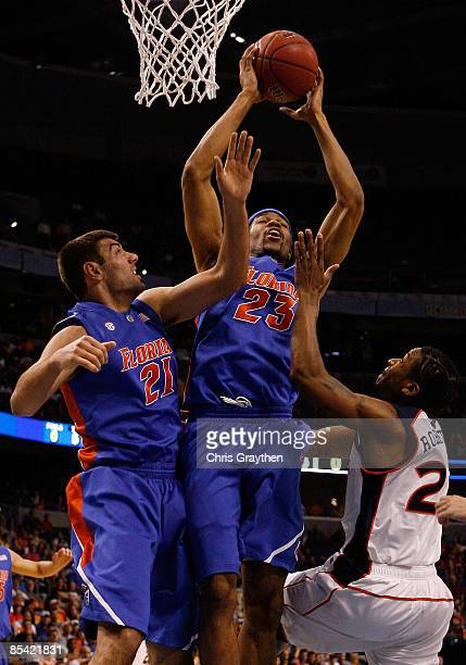 Alex Tyus and Dan Werner of the Florida Gators pull down a rebound over Quantez Robertson of the Auburn Tigers during the quaterfinal round of the...
