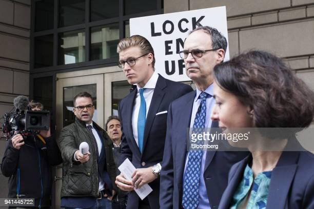 Alex Van der Zwaan former associate at Skadden Arps Slate Meagher Flom UK LLP center exits as a man holds a sign reading 'Lock Em Up' outside Federal...