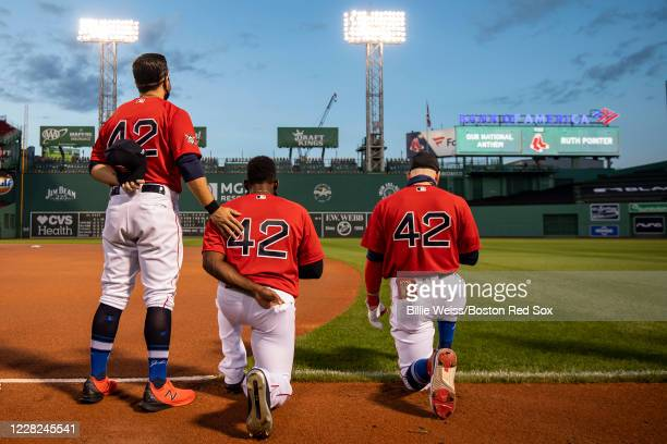 Alex Verdugo and Jackie Bradley Jr #19 of the Boston Red Sox kneel alongside Michael Chavis during the National Anthem during a pregame ceremony in...