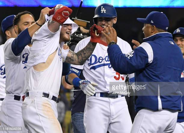 Alex Verdugo of the Los Angeles Dodgers celebrates with team mates who tore off his jersey after his 11th inning walkoff home run defeated the...