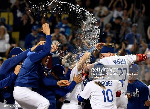 Alex Verdugo of the Los Angeles Dodgers is mobbed by teammates after hitting the game winning home run to defeat the Colorado Rockies 54 in eleven...