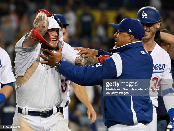 Alex Verdugo of the Los Angeles Dodgers is mobbed by teammates and manager Dave Roberts after hitting the game winning home run to defeat the...