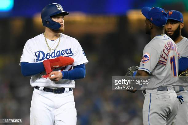 Alex Verdugo of the Los Angeles Dodgers walks past Adeiny Hechavarria of the New York Mets during a pitching change in the eighth inning at Dodger...