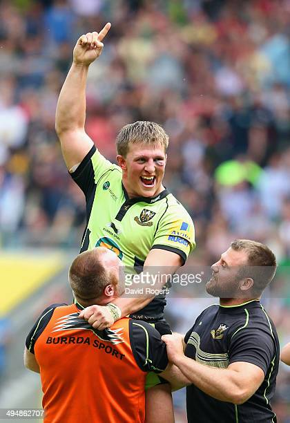 Alex Waller of Northampton Saints is lifted up by team mates after scoring the winning try in extra time during the Aviva Premiership Final between...