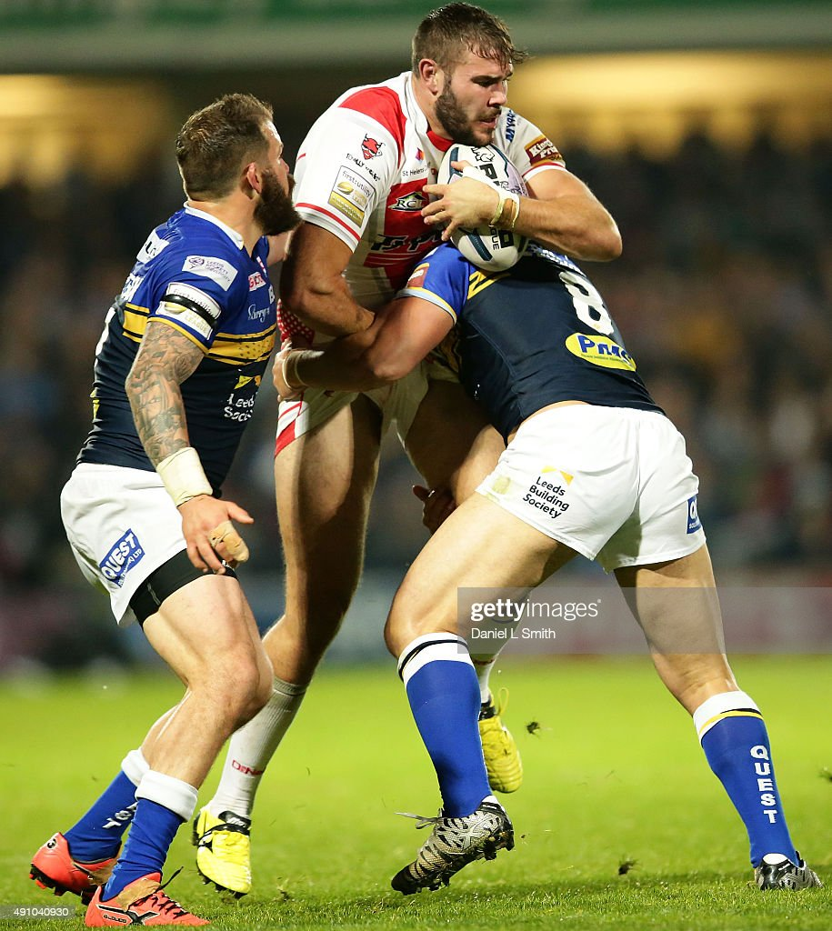Alex Walmsley of St. Helens R.F.C in possession is tackled by Kylie Leuluai and Adam Cutherbertson of Leeds Rhinos during the First Utility Super League Semi Final between Leeds Rhinos and St Helens at Headingley Carnegie Stadium on October 2, 2015 in Leeds, England.
