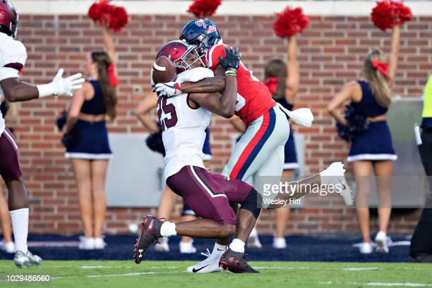 Alex Weber of the Mississippi Rebels catches a pass on the back of Madre Harper of the Southern Illinois Salukis at VaughtHemingway Stadium on...