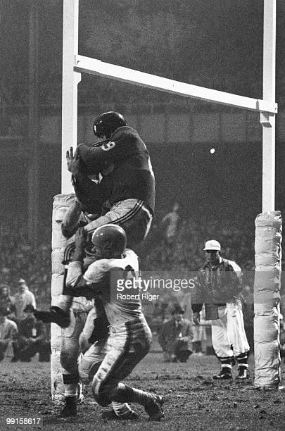 Alex Webster of the New York Giants catches a touchdown pass in the end zone as he is hit by Warren Lahr and a Cleveland Browns teammate during the...