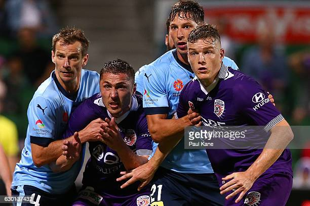 Alex Wilkinson and Filip Holosko of Sydney contest for position against Dino Djulbic and Shane Lowry of the Glory for a corner kick during the round...