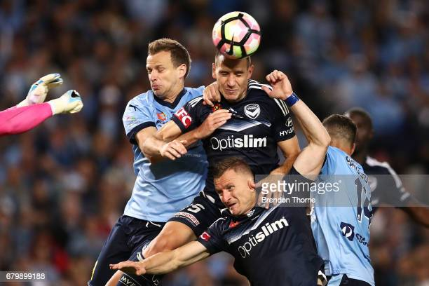 Alex Wilkinson of Sydney competes with Besart Berisha and Alan Baro of the Victory during the 2017 ALeague Grand Final match between Sydney FC and...