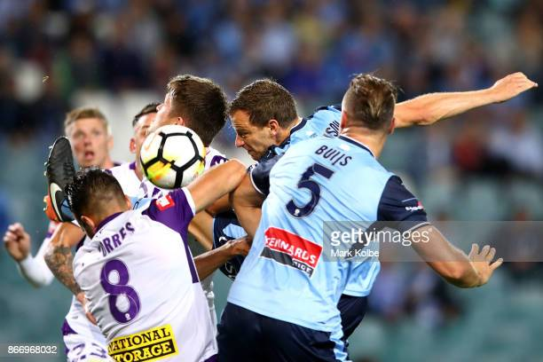 Alex Wilkinson of Sydney FC heads the ball at goal under pressure for the Glory defenders during the round four ALeague match between Sydney FC and...