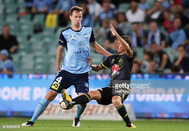 Alex Wilkinson of Sydney FC is challenged by Nathan Burns of Wellington Phoenix during the round 19 ALeague match between Sydney FC and the...