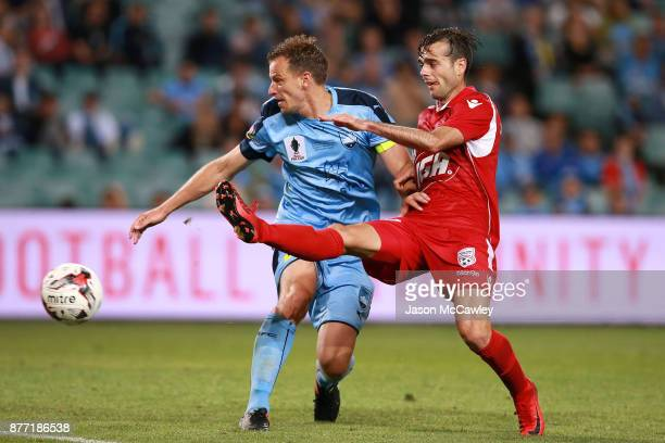 Alex Wilkinson of Sydney is challenged by Nikola Mileusnic of Adelaide during the FFA Cup Final match between Sydney FC and Adelaide United at...
