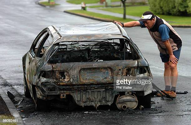 Alex Wong looks over his burned out Honda Civic in Northpark Ave Botany Downs after it was set alight in an arson attack that involved a further 10...