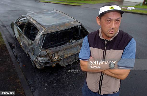 Alex Wong stands next to his burned out Honda Civic in Northpark Ave Botany Downs after it was set alight in an arson attack that involved a further...