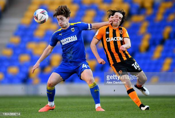 Alex Woodyard of AFC Wimbledon battles for possession with George Honeyman of Hull City during the Sky Bet League One match between AFC Wimbledon and...