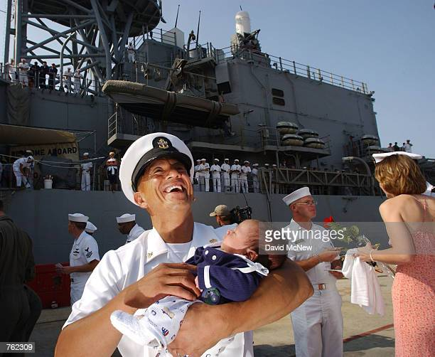 Alex Yano holds his fourweekold daughter Chase for the first time as the SPRUANCEclass Strike Destroyer USS Elliot returns to San Diego Harbor after...