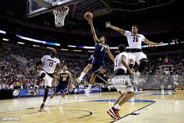 Alex Young of the UC Irvine Anteaters drives to the basket against Mangok Mathiang and Wayne Blackshear of the Louisville Cardinals in the second...