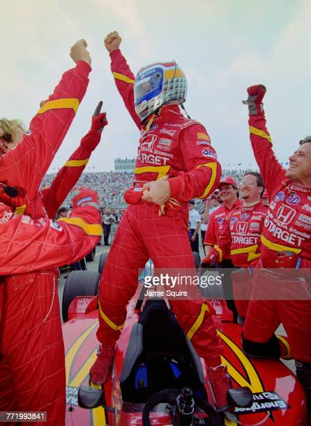 Alex Zanardi of Italy and driver of the Target Chip Ganassi Racing Reynard 98i Honda stands on top of his car and celebrates with his crew after...