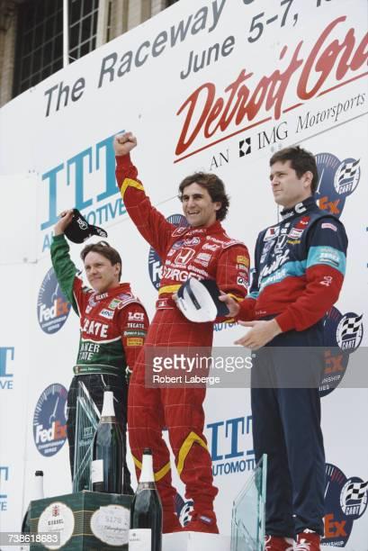 Alex Zanardi of Italy driver of the Target Ganassi Racing Reynard 98i Honda salutes in celebration alongside second placed Adrian Fernandez and third...