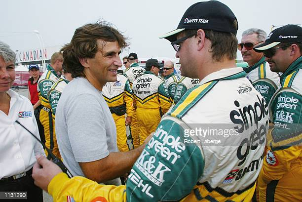 Alex Zanardi stands and greets members of the CART Simple Green Safety Team on July 6 2002 that helped him survive his accident at the American...