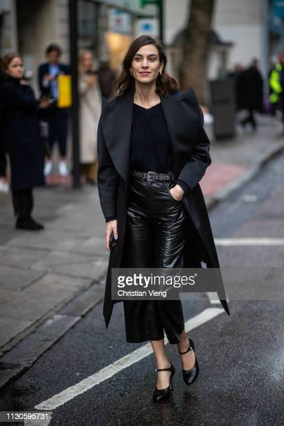 Alexa Chug wearing black coat cropped vinyl pants heels is seen outside Christopher Kane during London Fashion Week February 2019 on February 18 2019...