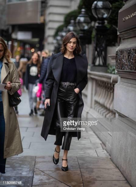 Alexa Chug wearing black coat cropped vinyl pants heels is seen outside Christopher Kane during London Fashion Week February 2019 on February 18 2019...