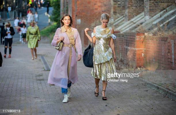 Alexa Chung is seen wearing pink brown sheer two tone trench coat and Pixie Geldof wearing golden dress outside Rocha during London Fashion Week...