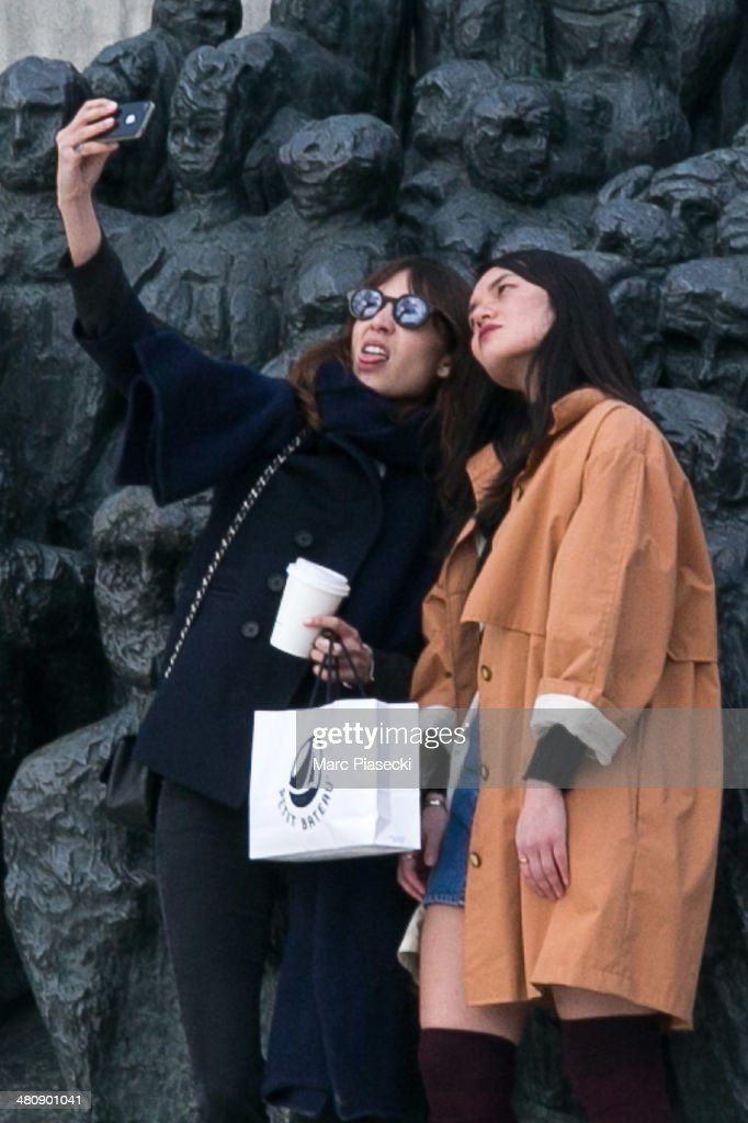 Alexa Chung (L) takes a selfie with a friend in the 'Jardins des Tuileries' on March 27, 2014 in Paris, France.