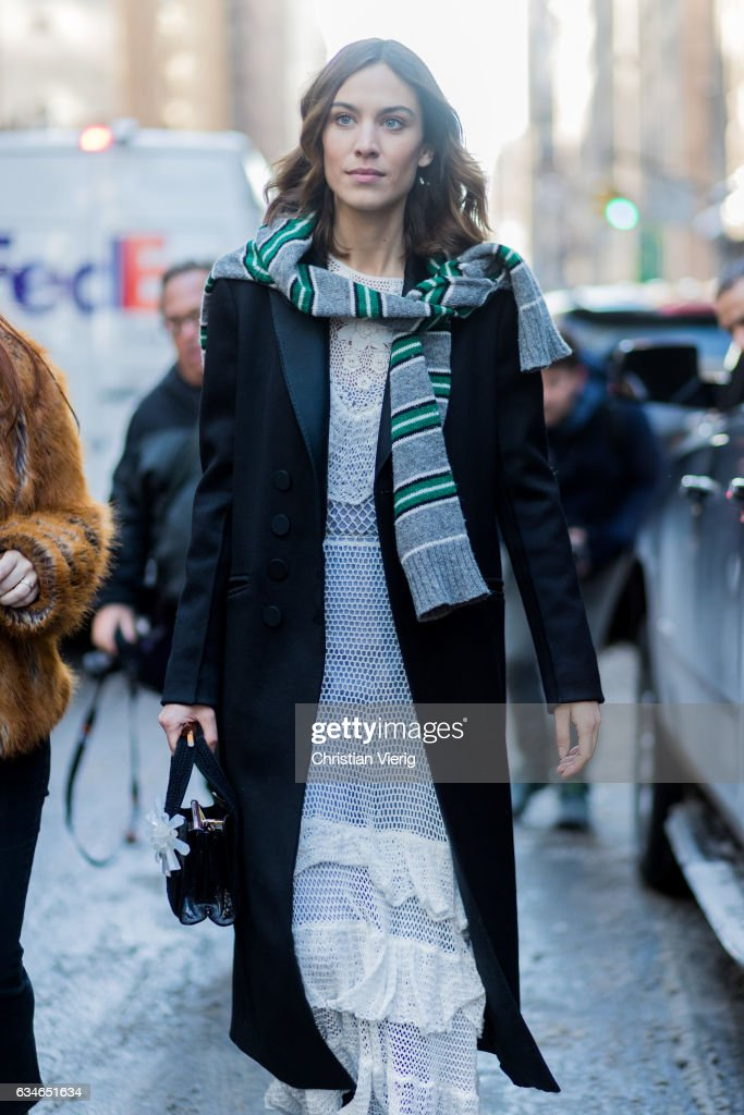 Alexa Chung wearing a trench coat, white laced dress, knit around her shoulders outside Calvin Klein on February 10, 2017 in New York City.