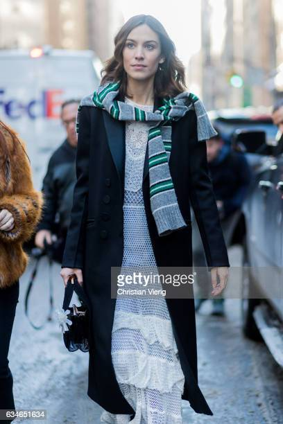 Alexa Chung wearing a trench coat white laced dress knit around her shoulders outside Calvin Klein on February 10 2017 in New York City