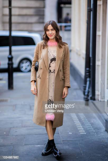 Alexa Chung wearing black bag beige wool coat dress with pink collar is seen during London Fashion Week September 2018 on September 17 2018 in London...