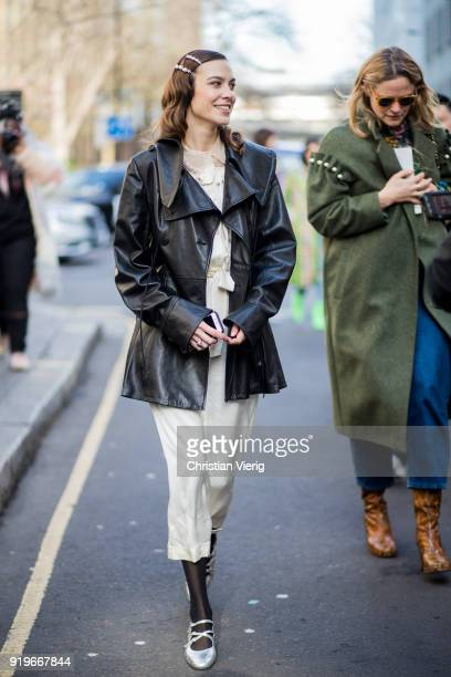 Alexa Chung wearing dress black leather coat seen outside Simone Rocha during London Fashion Week February 2018 on February 17 2018 in London England