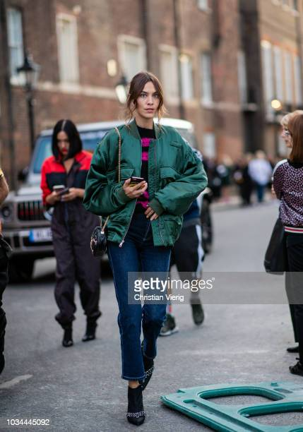 Alexa Chung wearing green bomber jacket cropped denim jeans seen outside Simone Rocha during London Fashion Week September 2018 on September 16 2018...