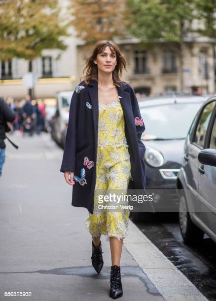 Alexa Chung wearing yellow dress wool coat seen outside Valentino during Paris Fashion Week Spring/Summer 2018 on October 1 2017 in Paris France