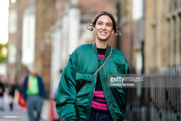 Alexa Chung wears a green bomber jacket blue denim flared pants during London Fashion Week September 2018 on September 16 2018 in London England