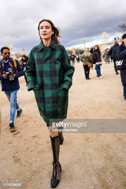 Alexa Chung wears a long green checked trench coat black mesh high boots outside Dior during Paris Fashion Week Womenswear Fall/Winter 2020/2021 on...