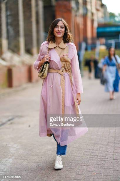 Alexa Chung wears a pale pink transparent trench coat with a beige part a belt a bag blue jeans white sneakers during London Fashion Week September...