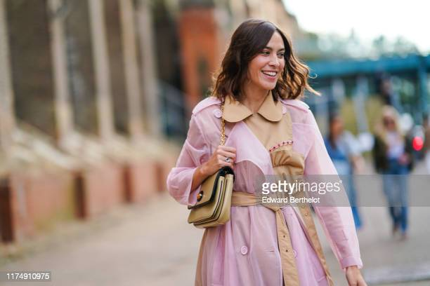 Alexa Chung wears a pale pink transparent trench coat with a beige part a belt a bag blue jeans during London Fashion Week September 2019 on...