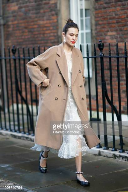 Alexa Chung wears earrings, a pale brown / beige long wool coat, a white lace mesh dress, black bejeweled shoes, during London Fashion Week Fall...