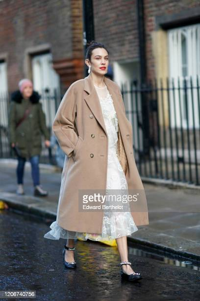 Alexa Chung wears earrings a pale brown / beige long wool coat a white lace mesh dress black bejeweled shoes during London Fashion Week Fall Winter...